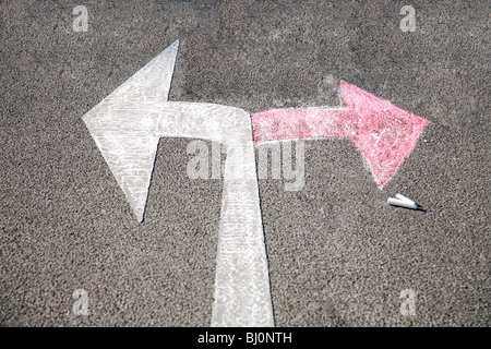 red arrow drawn on road in opposite direction of road sign - Stock Photo