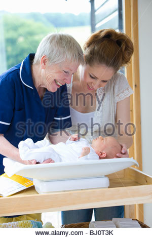 Nurse weights newborn boy as mother watches on - Stock Photo