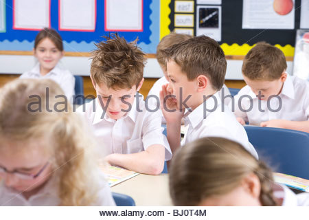 School boys whispering secrets in classroom - Stock Photo