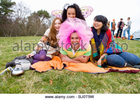 Laughing friends in silly costumes attending outdoor festival - Stock Photo