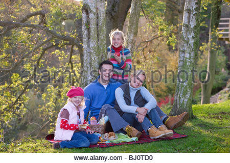 Mother, father and daughters having picnic outdoors - Stock Photo