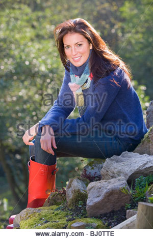 Smiling woman in rubber boots sitting on rocks - Stock Photo