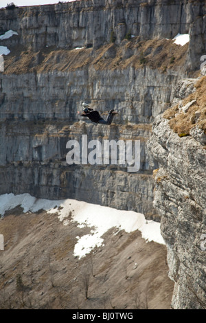 BASE jump from a cliff. The ultimate kick to do an object jump with a forward-down position into the deep valley. - Stock Photo