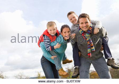 Parents giving children piggyback rides outdoors - Stock Photo