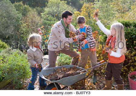 Laughing family playing with autumn leaves outdoors - Stock Photo