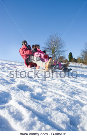 Excited father and daughter sledding down snowy hill on sled - Stock Photo