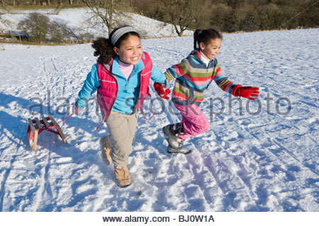 Excited sisters sledding on snowy hill - Stock Photo