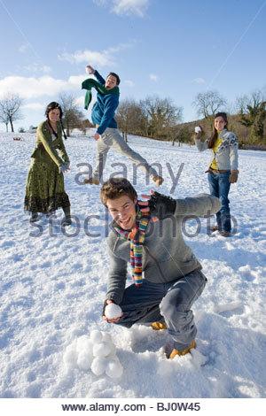 Friends having snowball fight in snowy field - Stock Photo