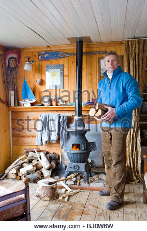 Man in living room putting log into wood burning stove - Stock Photo