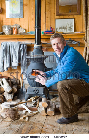 Man warming himself by wood burning stove - Stock Photo