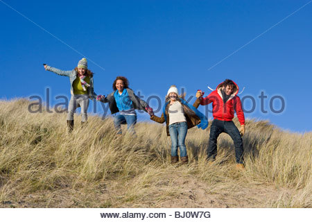 Excited friends running down sand dune - Stock Photo