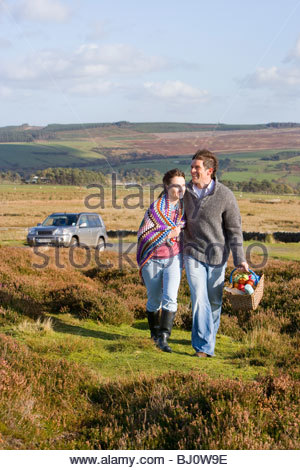 Happy couple on picnic carrying blanket and basket - Stock Photo