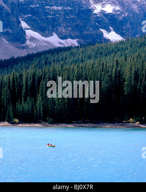 Couple canoeing on the aquamarine waters of Moraine Lake, Banff National Park, Alberta, Canada - Stock Photo