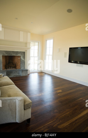 Large new New England living room with huge television and a fireplace. - Stock Photo