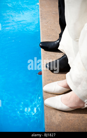 Cropped view of bride and groom standing near swimming pool - Stock Photo
