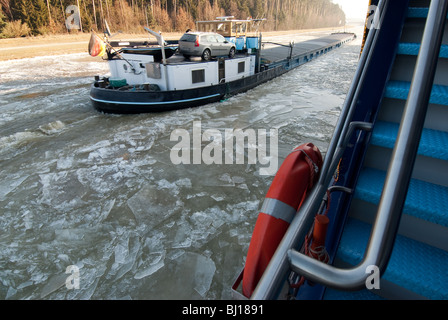 Ships passing on ice laden Main Danube Canal near Regensburg, Germany - Stock Photo