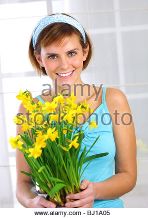young woman holding bunch of daffodils - Stock Photo