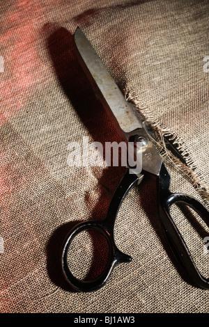 Large scissors in cut Hessian cloth. - Stock Photo