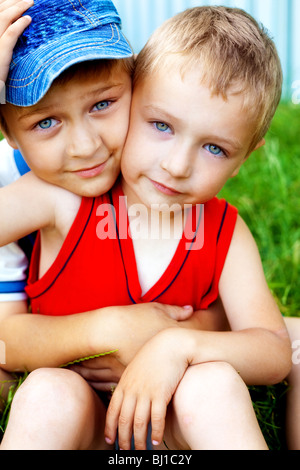 Hug of two cute loving brothers outdoors