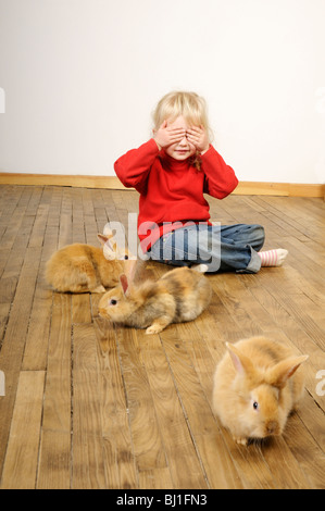 Stock photo of a four year old girl playing with her pet rabbits on a wooden floor. - Stock Photo