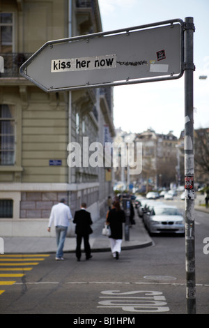 Kiss her now graffiti on the rear of a street sign, Geneva, Switzerland - Stock Photo