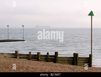 Wooden groyne on the beach at Leigh-on-Sea with a ship on the horizon. Leigh-on Sea, Essex, England - Stock Photo