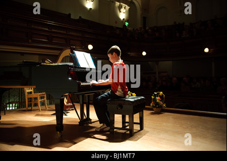 A young teenage boy competing in a music competition playing the grand piano in a small concert hall, UK - Stock Photo
