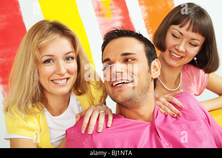 Group of three happy people sitting on sofa in a colorfully painted room - Stock Photo
