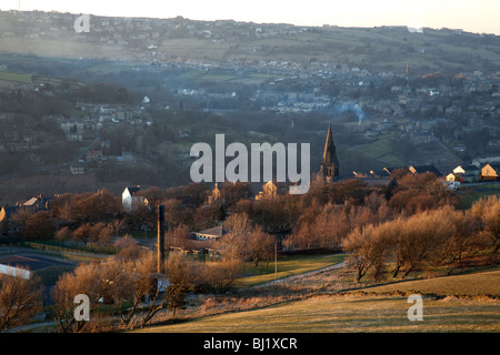 Yorkshire Pennine village nestling in the Colne valley on a bright cold still winter's evening - Stock Photo