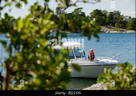Motorboat berthing at a rock in the Stockholm archipelago, Sweden. - Stock Photo