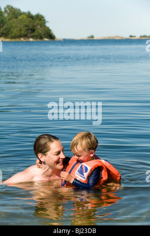 Boy in a life vest bathing with his mother, Sweden. - Stock Photo