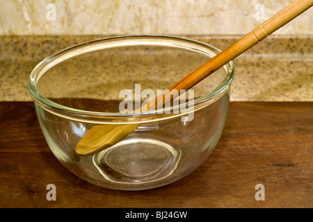 Wooden spoon in a large glass mixing bowl - Stock Photo