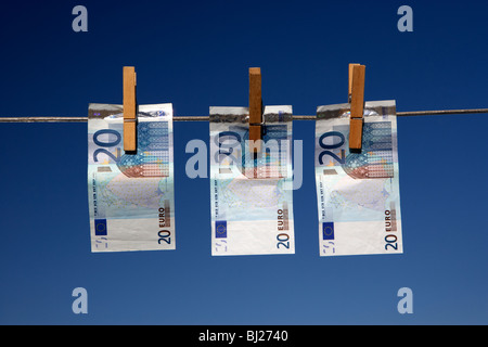 three twenty euro banknotes hanging on a washing line with blue sky - Stock Photo