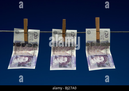 three twenty pounds sterling banknotes hanging on a washing line with blue sky - Stock Photo