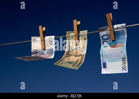 twenty pounds dollars euro banknotes hanging on a washing line with blue sky - Stock Photo