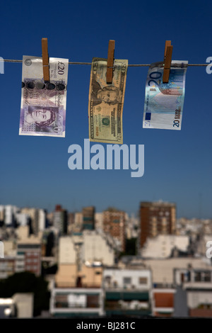 twenty pounds dollars euro banknotes hanging on a washing line with blue sky over city skyline Stock Photo