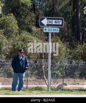 man walking dog under dog walk sign at rest area along I-75 Florida - Stock Photo