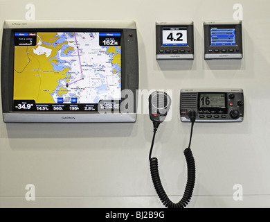 Simple marine navigation instrument consisting of GPS display with addition of Garmin's GMI system and VHF radio. - Stock Photo