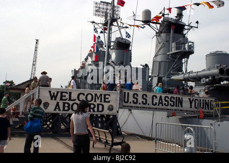 USS Cassin Young in Charlestown Navy Yard during Tall Ships festival. A long line of people wait to board WWII Navy - Stock Photo