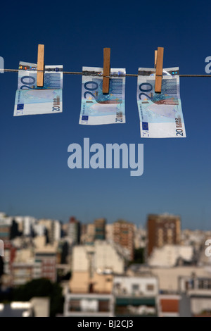 three twenty euro banknotes hanging on a washing line with blue sky over city skyline Stock Photo