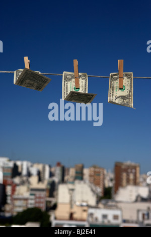 three one dollar bills blowing in the wind hanging on a washing line with blue sky over a city skyline - Stock Photo