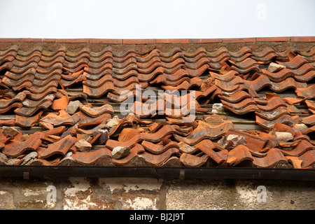 Broken and damaged terracotta tiles on a roof of an abandoned building - Stock Photo