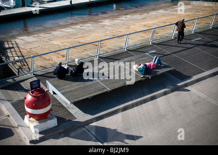 People relaxing in winter sunshine in Torquay,D Day Embarkation Ramps,The 4th US Infantry Division embarked from - Stock Photo