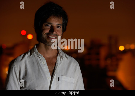hispanic latin man standing on roof terrace with evening city in the background in buenos aires argentina - Stock Photo