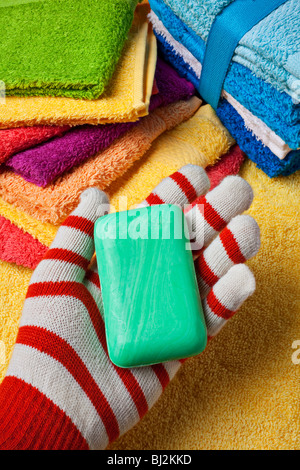 Gloved hand holding green bar of soap - Stock Photo