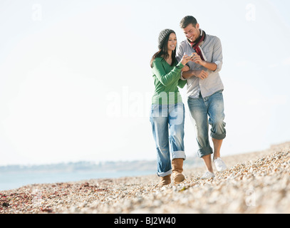 Young couple strolling on beach - Stock Photo