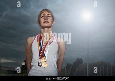 portrait of female athlete with medals - Stock Photo