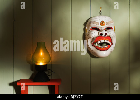 A Balinese dance mask and candle lamp scene. - Stock Photo