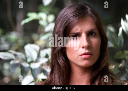 young hispanic latin woman looking angry or confused in a wooded area of argentina south america - Stock Photo