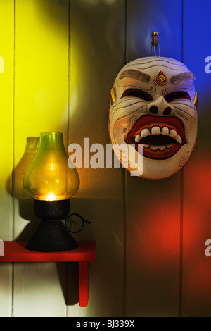 A Balinese dance mask and candle lamp. - Stock Photo